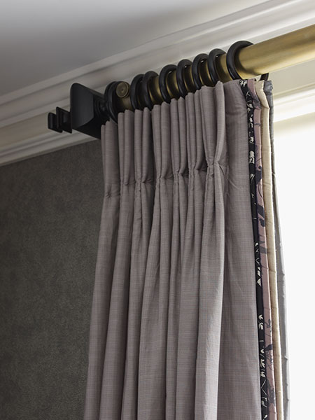Triple pinch pleat curtain with contrasting leading edges on an antique brass pole with wooden rings and finials