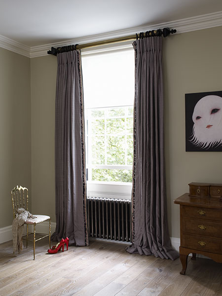 Triple pinch pleat headed curtains on an antique brass pole with wooden rings and finials