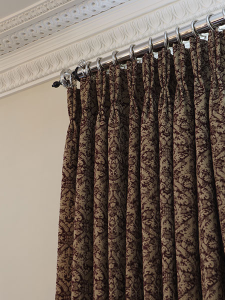 Triple pleat headed curtain on nickel curtain pole with nickel rings